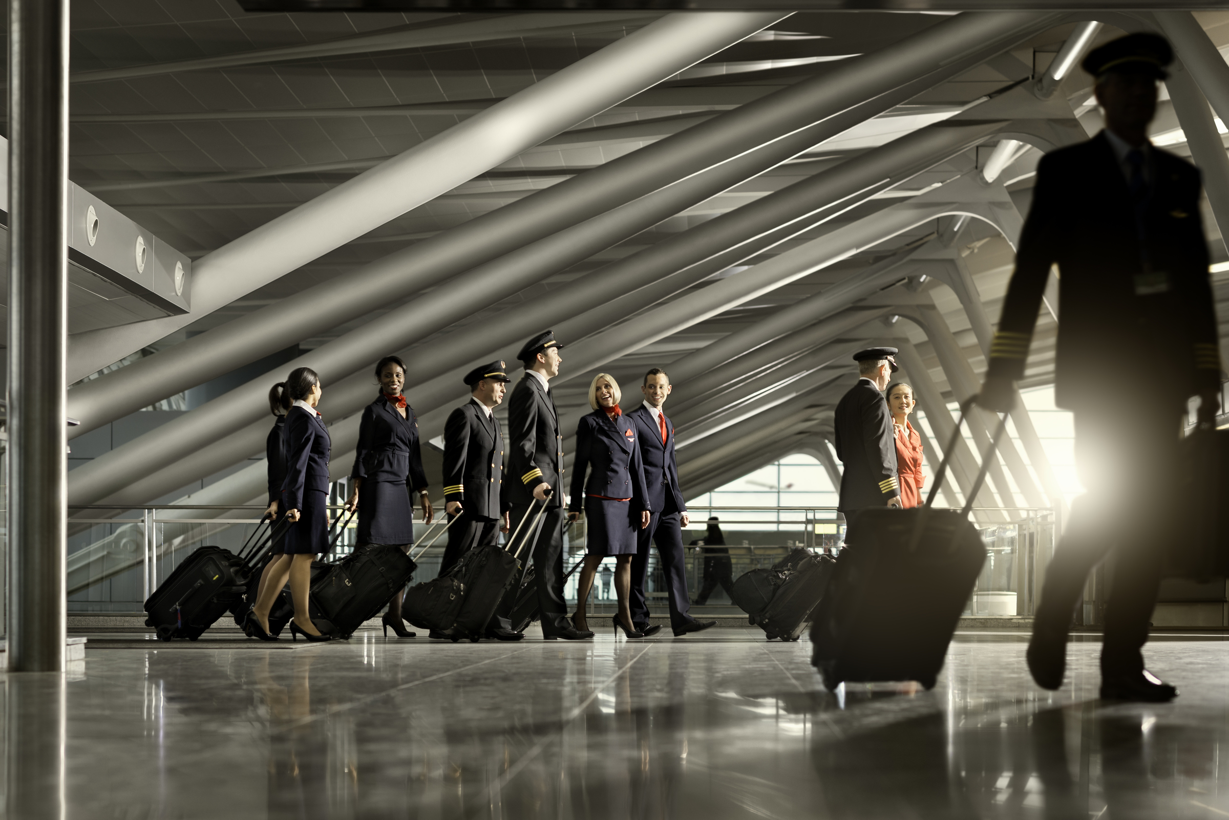 Flight Attendants and Pilots walking through airport with bags