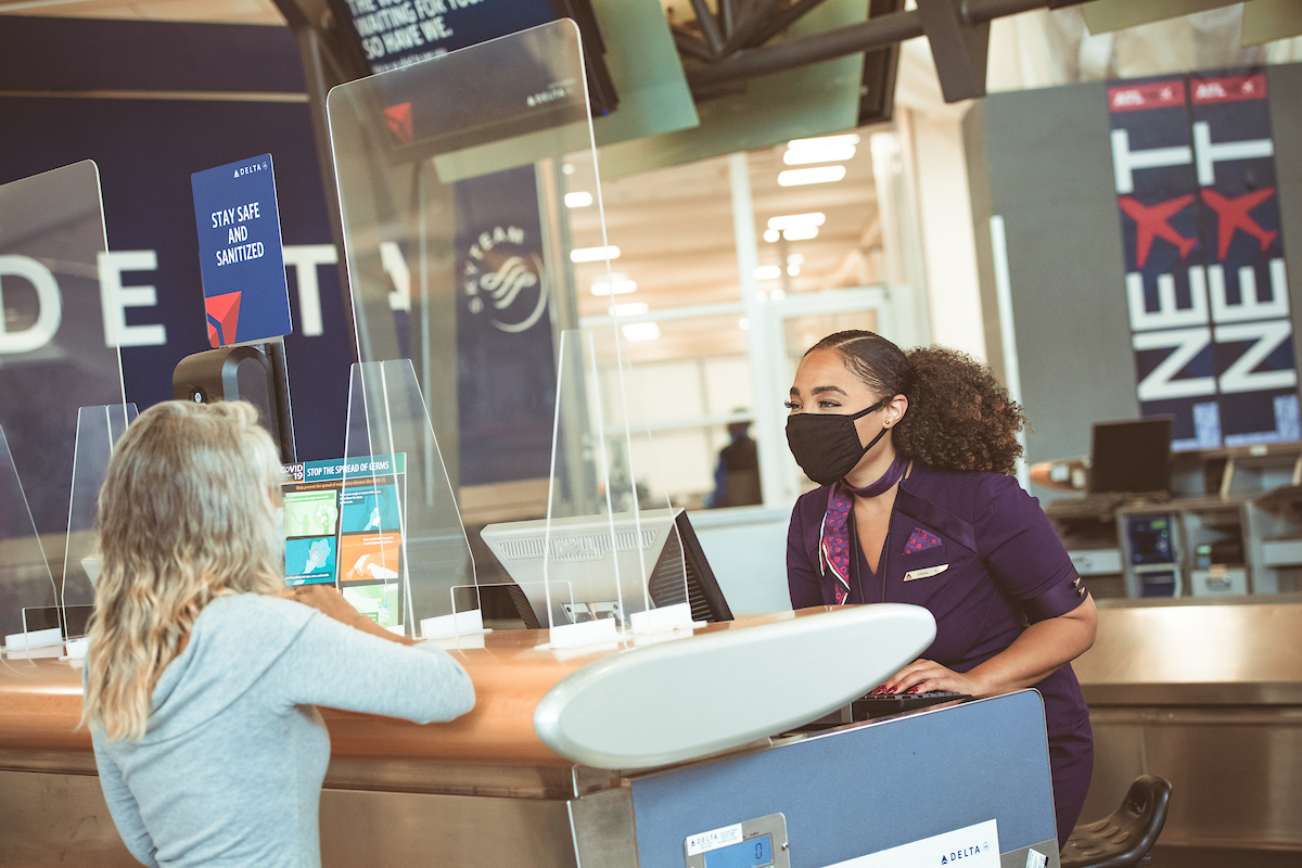 Delta employee and customer at ticket counter with mask