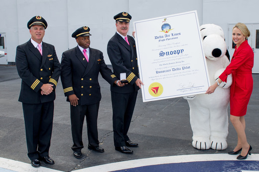 Pilots standing with Snoopy the character