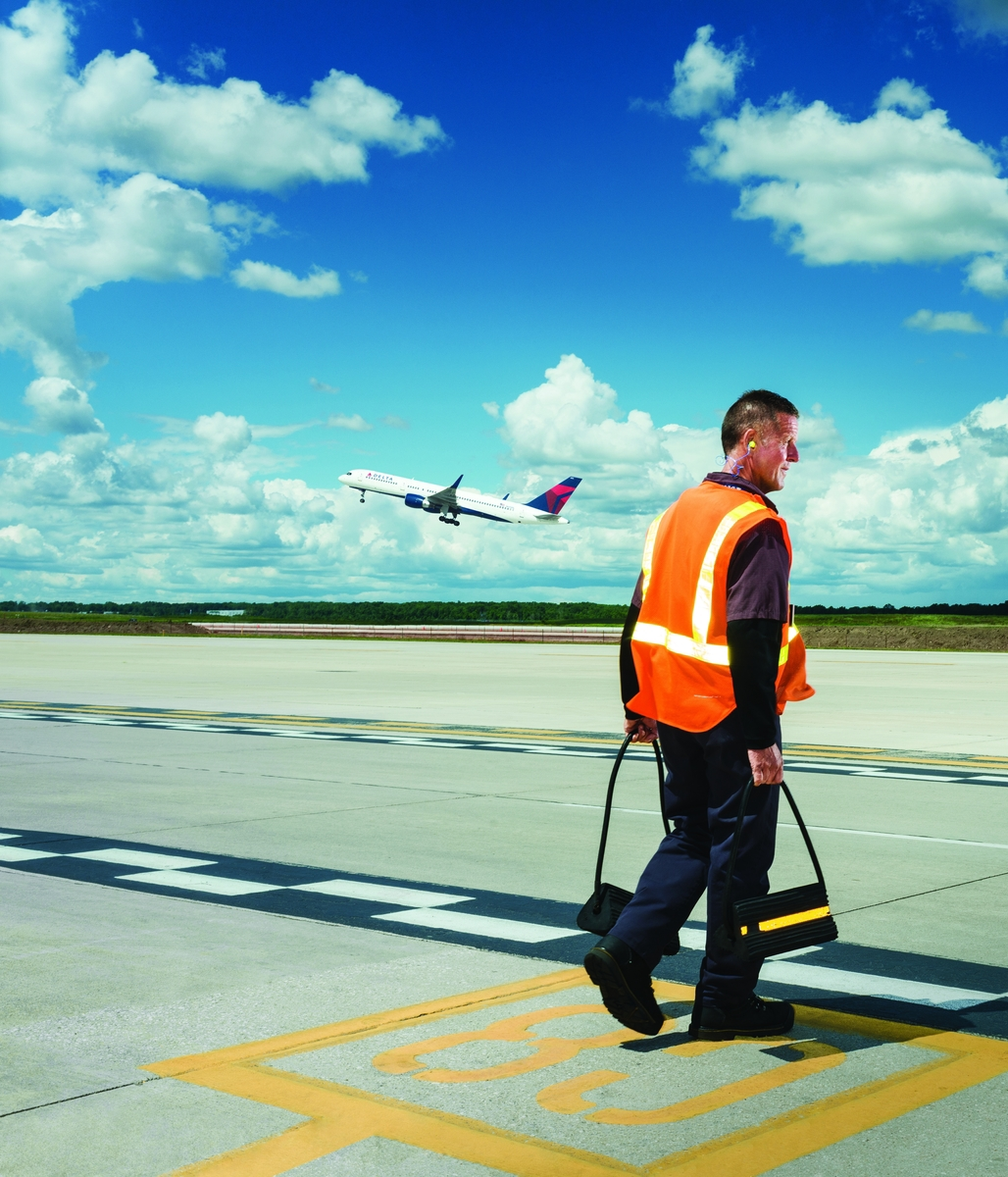 Employee on ramp with aircraft in flight