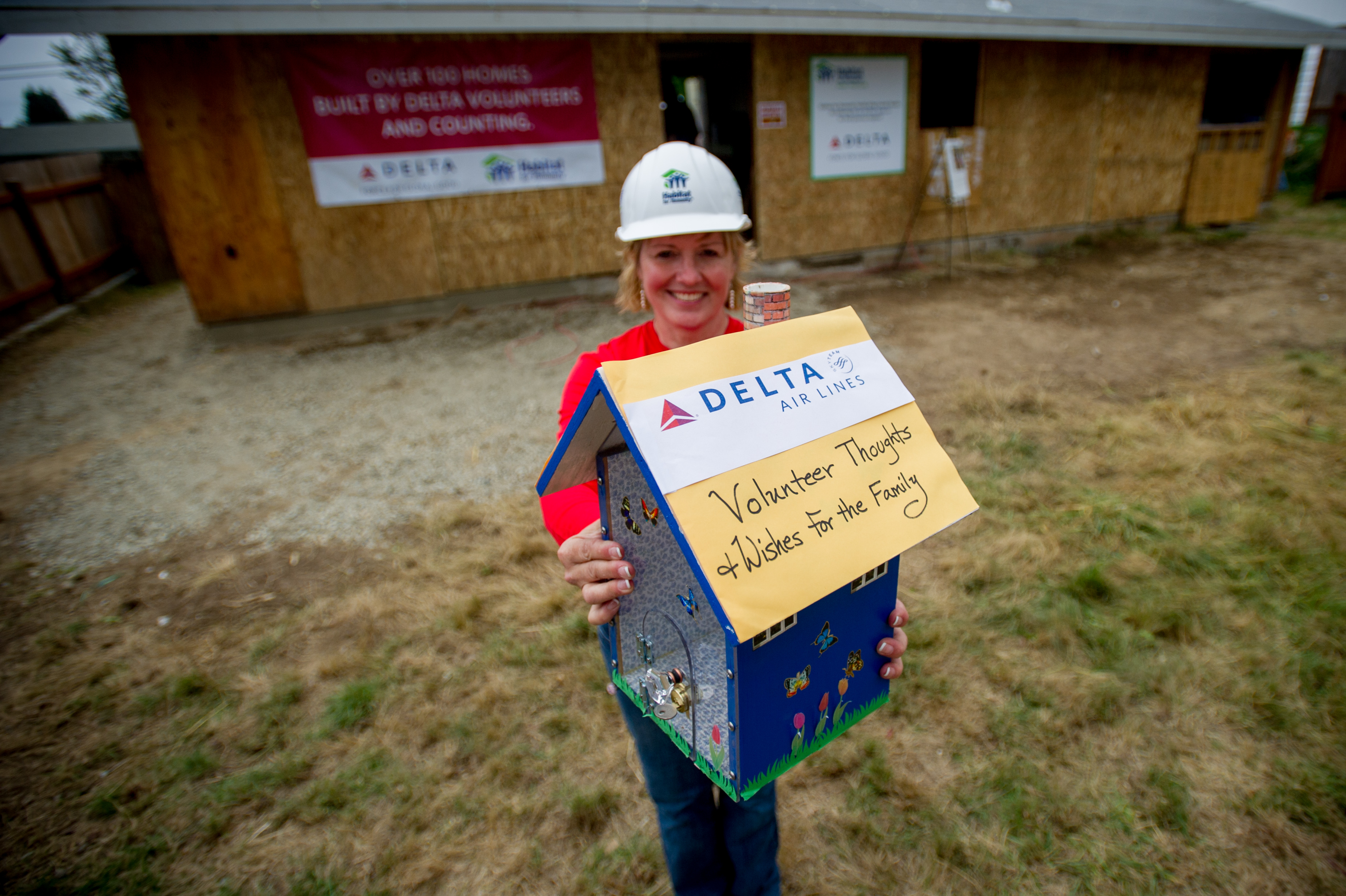 group of Employees after building for habitat for humanity - Woman holding a small model house