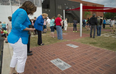 People looking at bricks outside of Delta Flight Museum