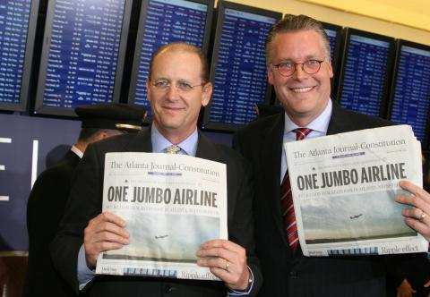 Richard Anderson and Ed Bastian holding up newspapers