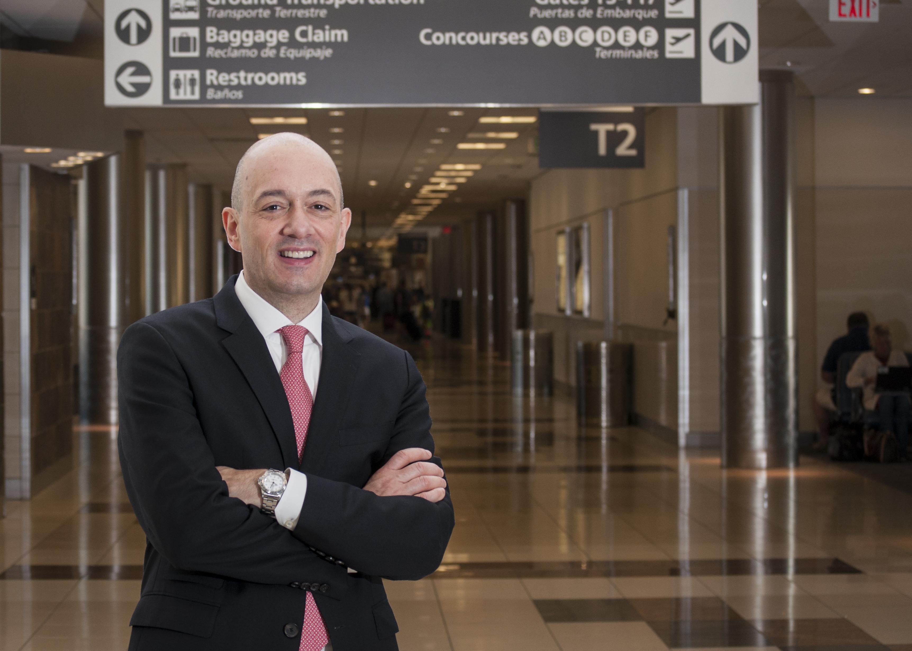 Man standing in airport - Nicolas Ferri