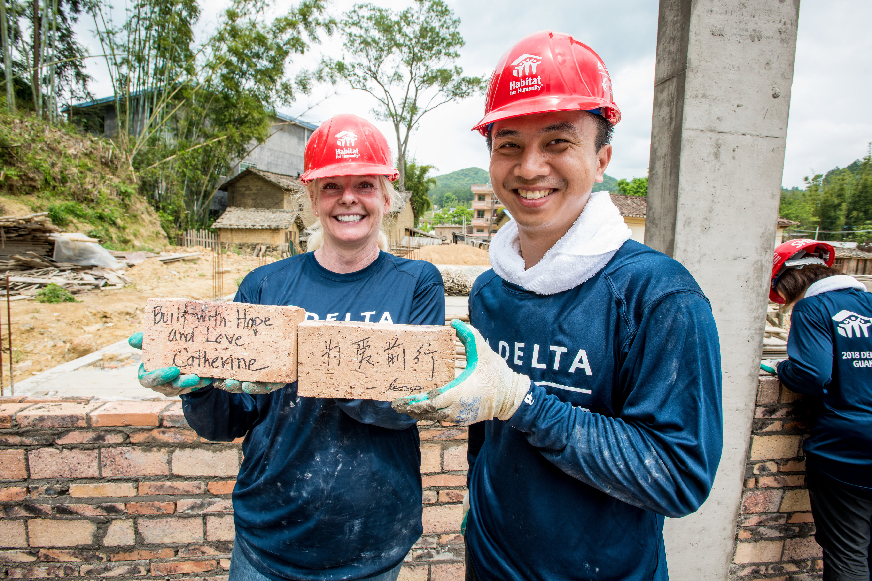 "Global Build volunteers with ""Built with Hope and Love"" bricks"