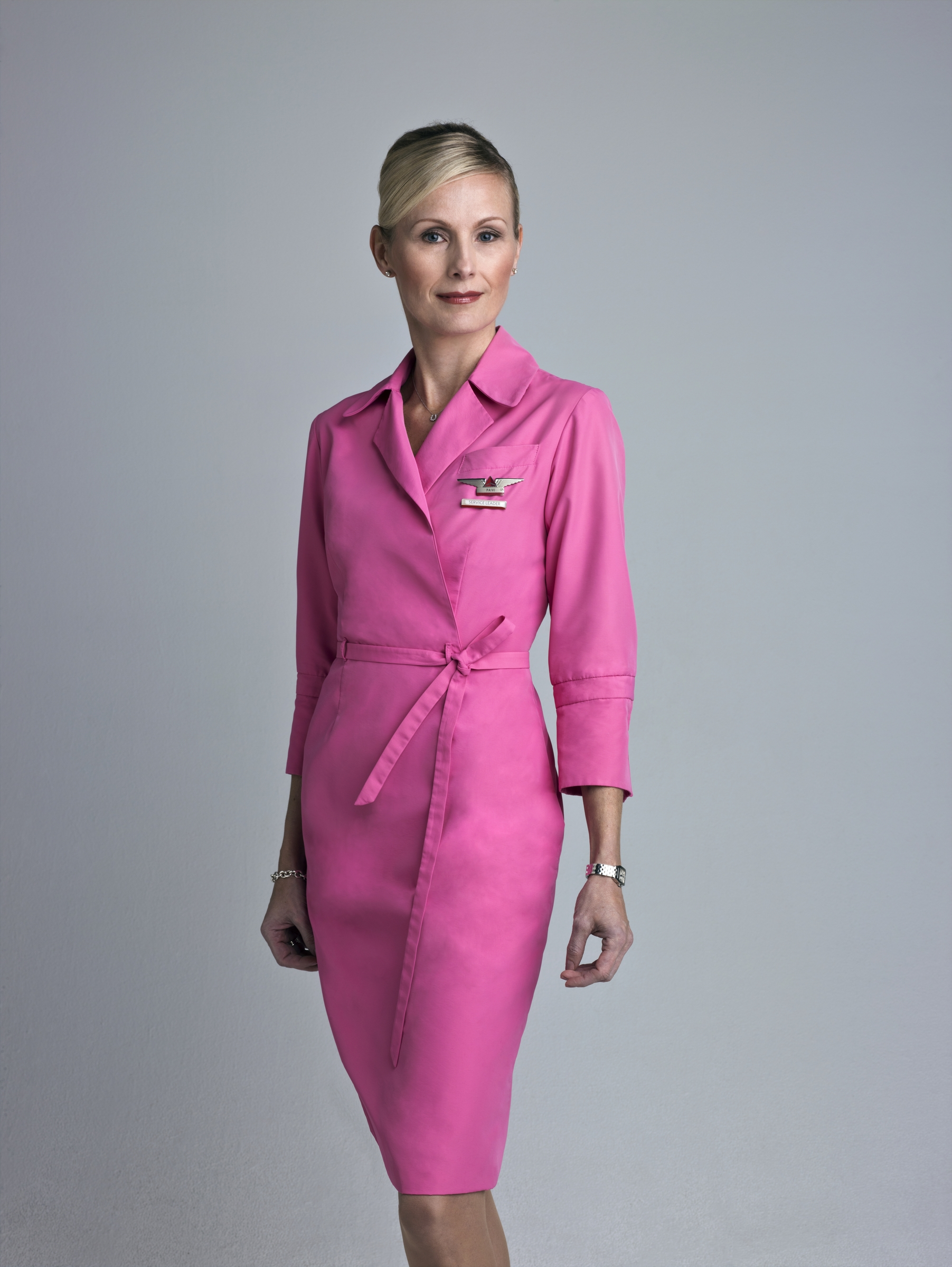 """One little pink dress, one huge statement - Woman standing in pink flight attendant unform"