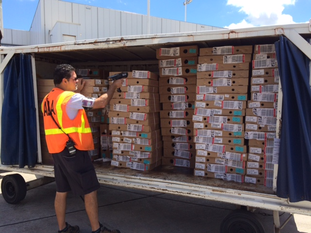 FLL Aircraft Load Agent Dennis Carmona scans several dozen parcels of flowers bound for MSP this week.