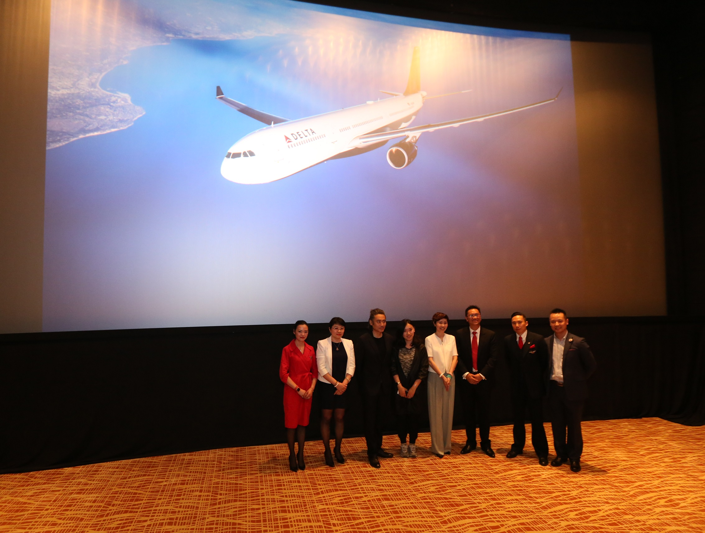 People standing in front of large screen