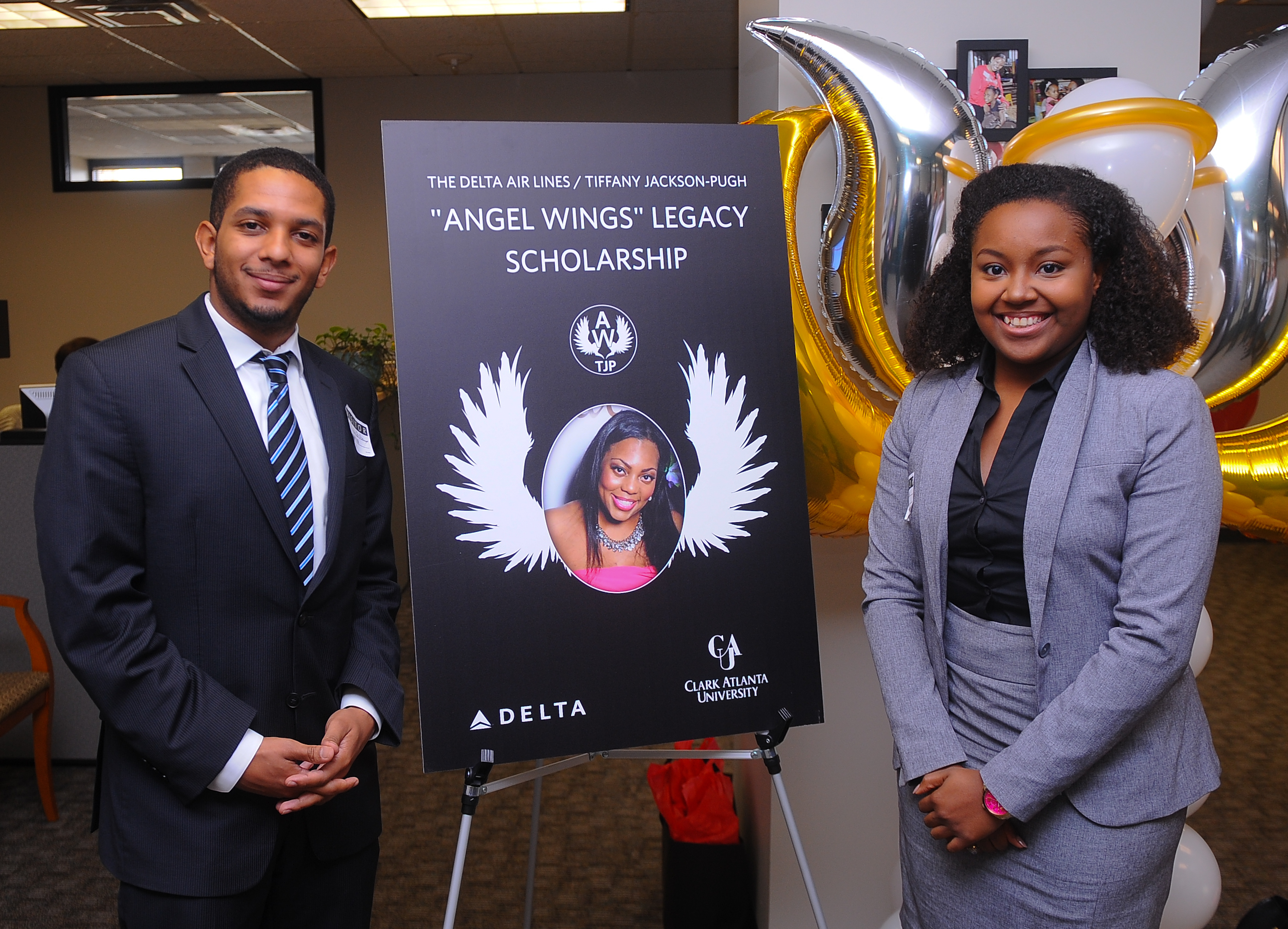 Angel Wings Scholarship sign with 2 people standing beside it