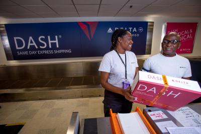 Delta DASH employees with pink package