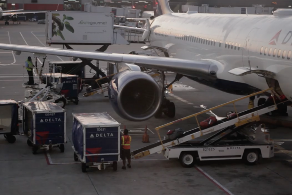 B-roll san juan humanitarian video still image. image of a man loading baggage on to a plane