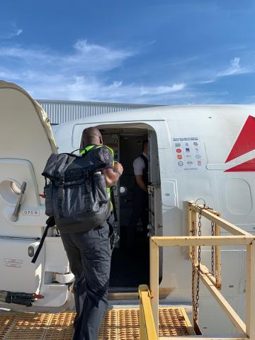 Delta employee boarding aircraft bound for Bahamas