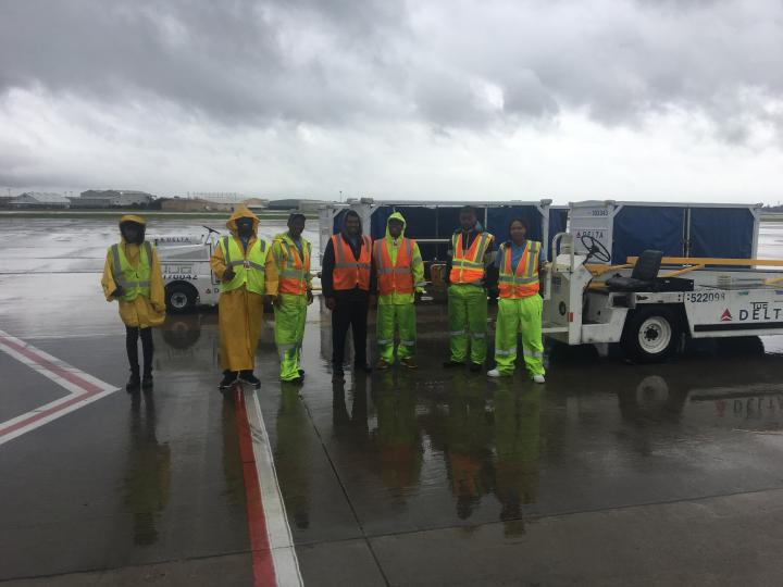 Employees on ramp donning rain gear