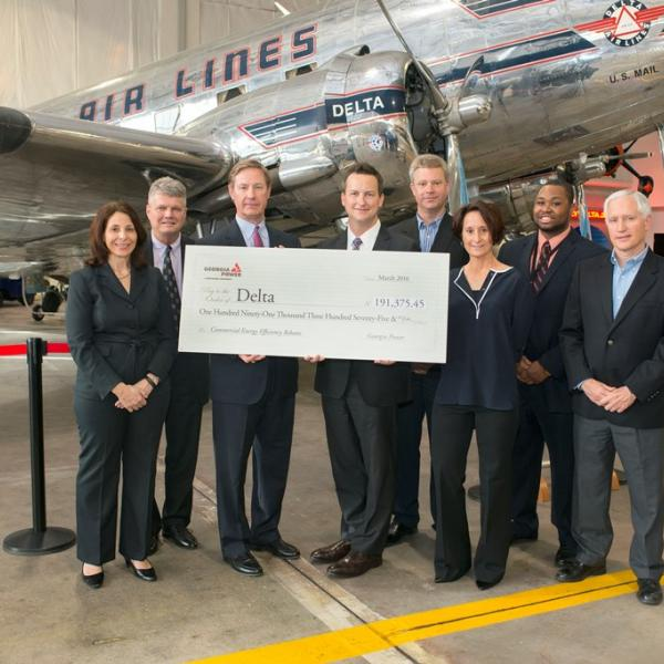group of people holding a check