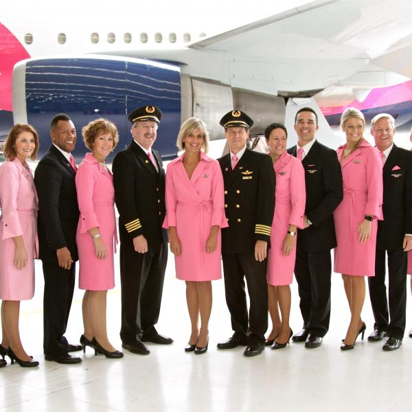 Flight Attendants and Pilots standing in front of pink plane